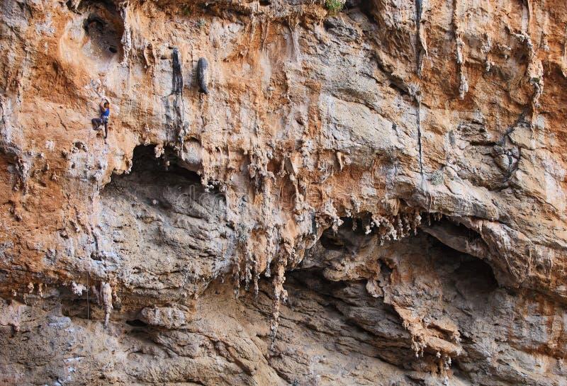 Weiblicher Felsenbergsteiger auf einem Klippengesicht stockbilder