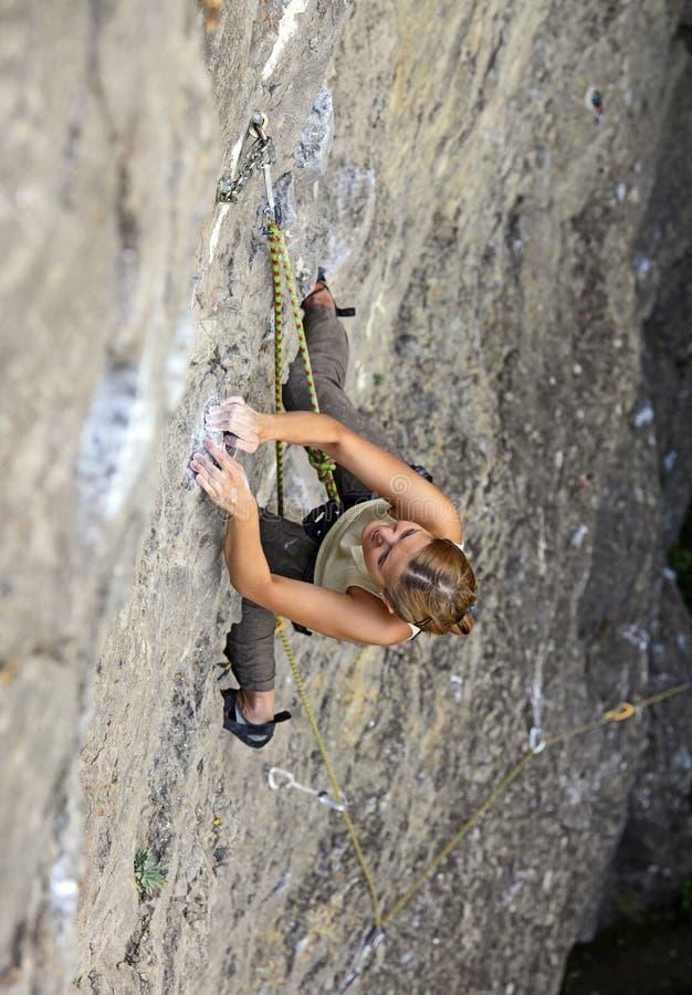 Weiblicher Felsenbergsteiger, der ihre Methode herauf eine Klippe kämpft stockfoto