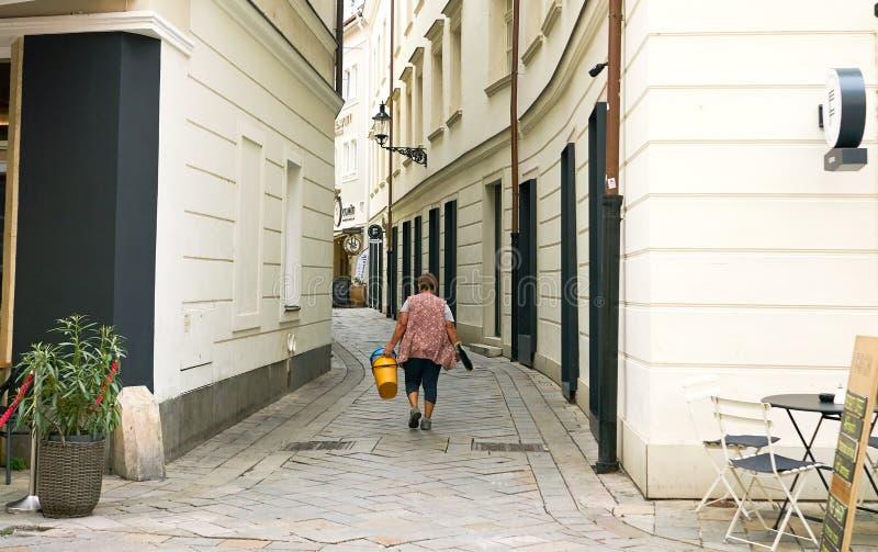Weiblicher Fensterputzer geht in alte Stadt Bratislava, Slowakei lizenzfreie stockbilder