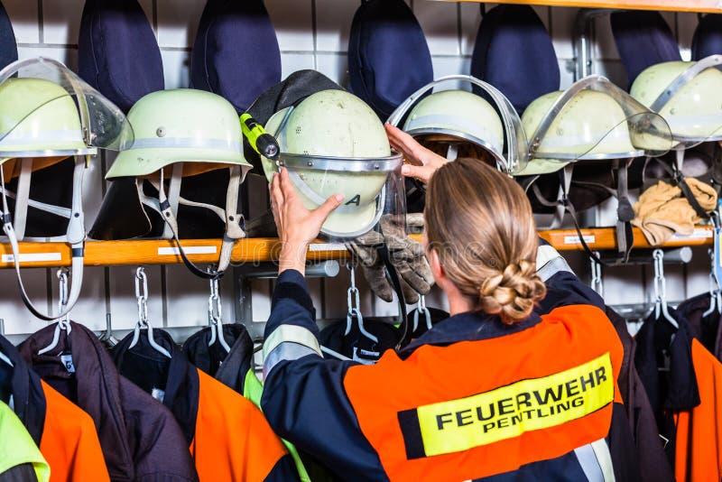 Weiblicher Feuerwehrmann im Umkleideraum, der Sturzhelm nimmt stockbilder