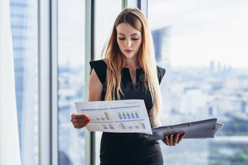 Weiblicher Finanzanalytiker, der die Papiere studieren die Dokumente stehen gegen Fenster mit Stadtansicht hält stockfotografie