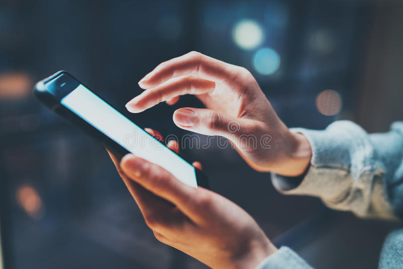 Weiblicher Finger, der auf Schirm Smartphone auf Hintergrundbeleuchtungsglühen bokeh Licht in der Nacht atmosphärisch zeigt horiz stockfotos