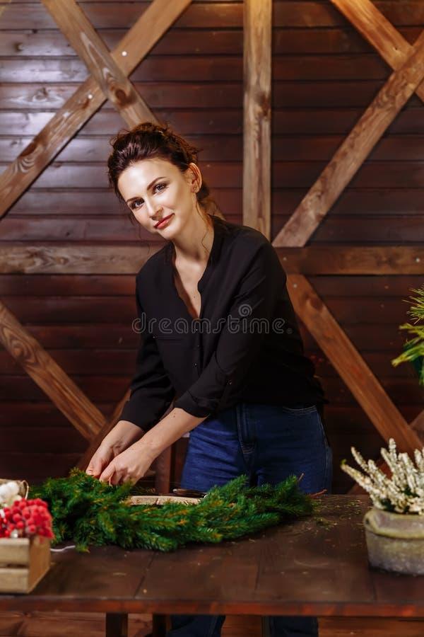 Weiblicher Florist, der Weihnachtskranz im Blumenladen verziert Frau, die Schmuck für Weihnachtsfeiertage macht Herstellung des D stockbild