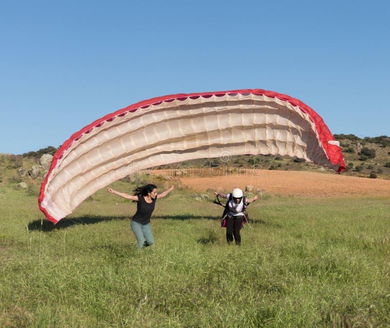 Weiblicher Fluglehrer, eine Frau unterrichtend, sich mit einem Gleitschirm zu entfernen stockfotografie