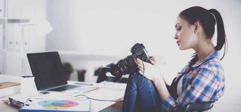 Weiblicher Fotograf, der auf dem Schreibtisch mit Laptop sitzt stockfotografie