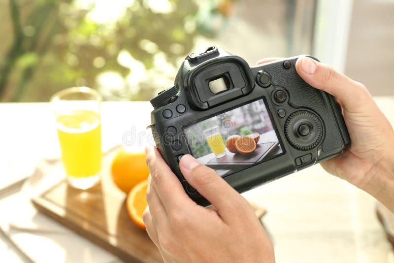 Weiblicher Fotograf, der Foto des Safts und der Orangen mit Berufskamera macht stockfotos