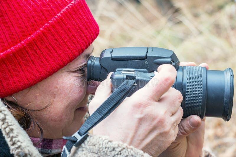 Weiblicher Fotograf, der im Sucher schaut stockbild