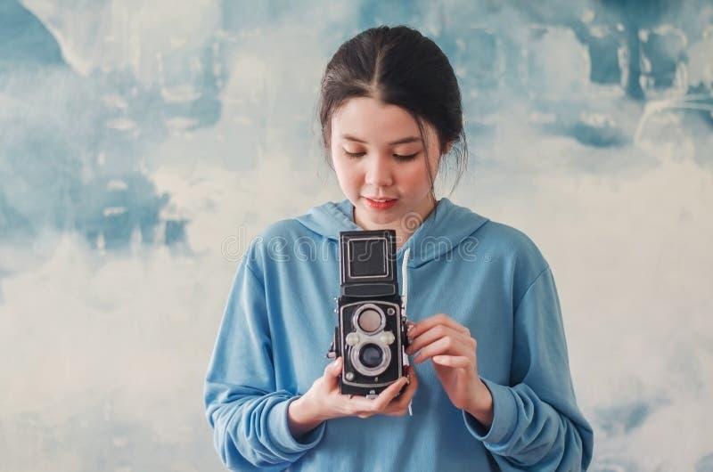 Weiblicher Fotograf der stilvollen Weinlese, der ihre alte Doppellinsenkamera zu ihrem Kasten hält, wie sie ihr Bild mit einem er lizenzfreies stockbild