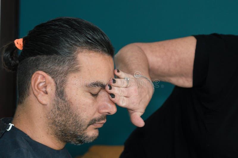 Weiblicher Friseur, der das Gesicht des jungen Mannes mit ihrer Hand säubert, nachdem sein Haar rasiert worden ist lizenzfreies stockbild