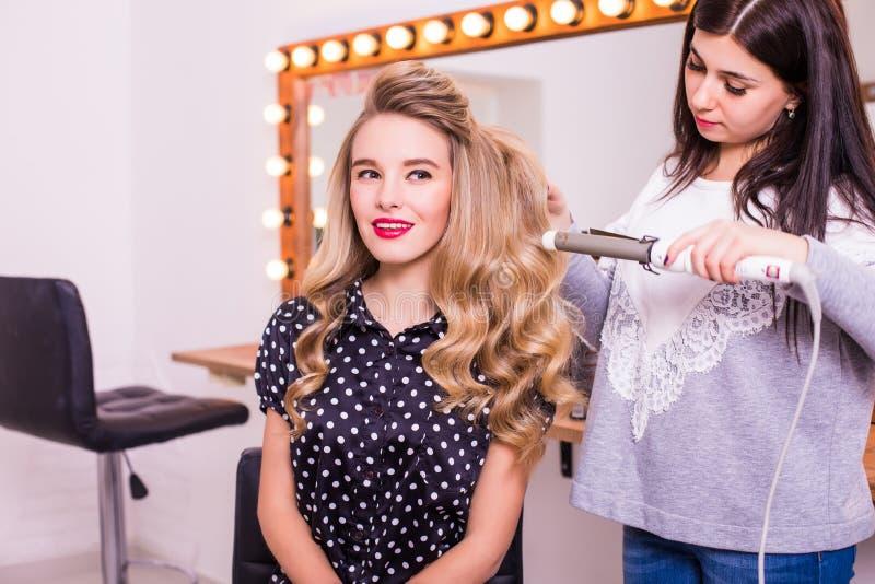 Weiblicher Friseur, der der netten reizenden jungen Frau Frisur steht und macht stockfoto