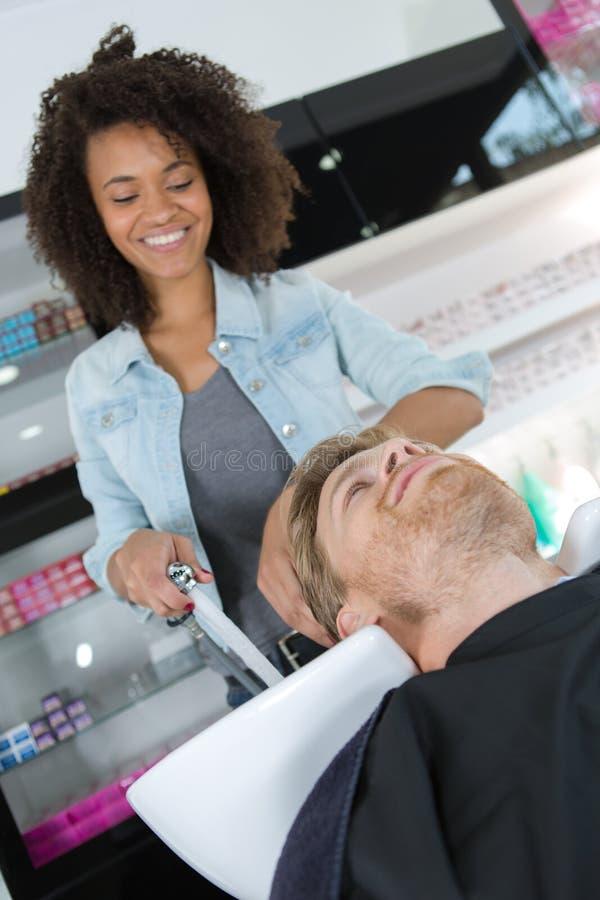 Weiblicher Friseur, der Frisur für männlichen Kunden macht stockfoto