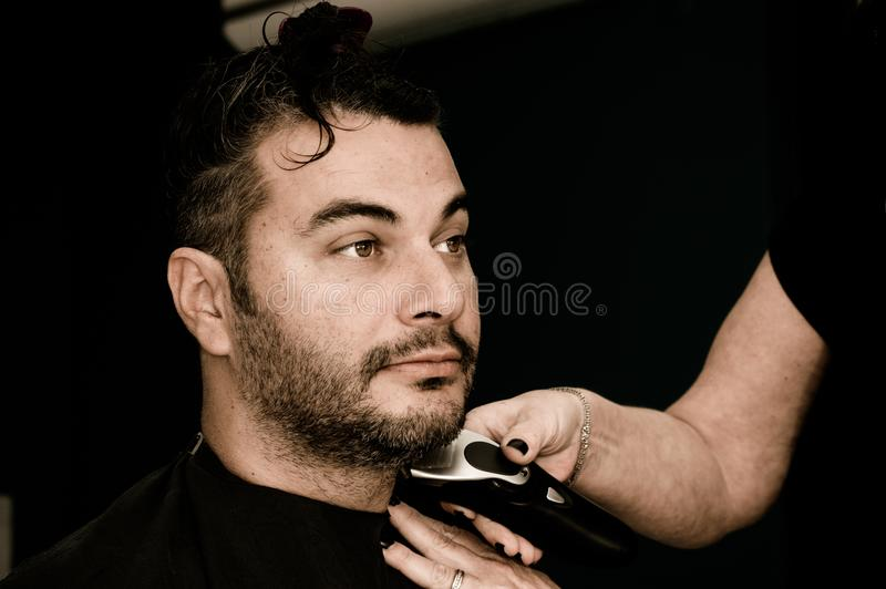 Weiblicher Friseur, der mit dem Haarscherer, das Gesicht des jungen Mannes rasierend arbeitet stockbild