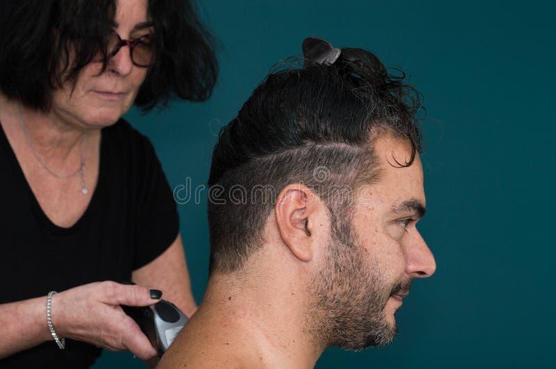 Weiblicher Friseur, der mit dem Haarscherer, den Hals des jungen Mannes rasierend arbeitet stockfoto