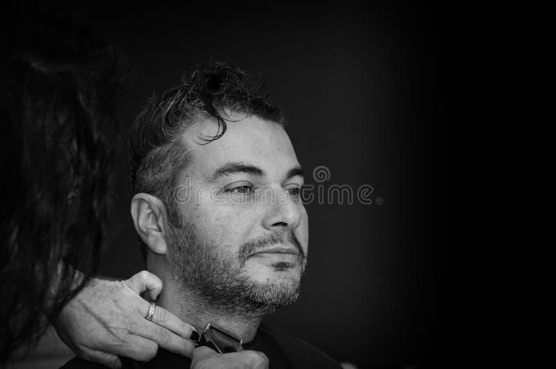 Weiblicher Friseur, der mit dem Haarscherer, den Hals des jungen Mannes rasierend arbeitet lizenzfreies stockfoto