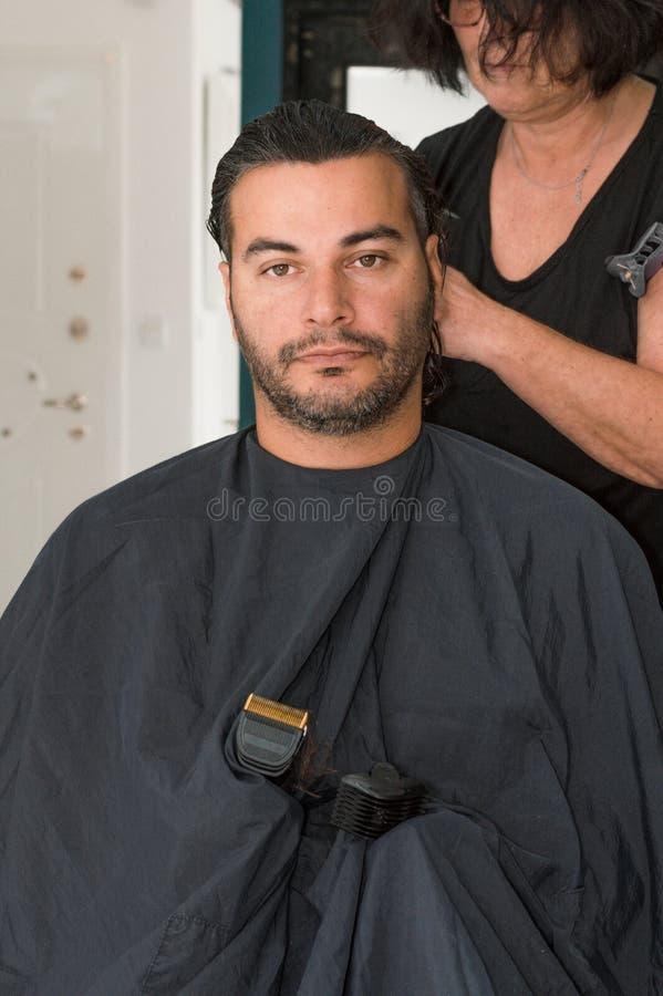 Weiblicher Friseur, der mit dem Haarscherer, jungen Männerkopf kämmend arbeitet lizenzfreies stockfoto