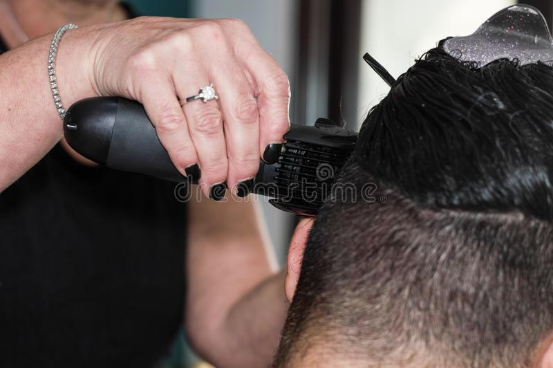 Weiblicher Friseur, der mit dem Haarscherer, jungen Männerkopf rasierend arbeitet lizenzfreie stockfotografie