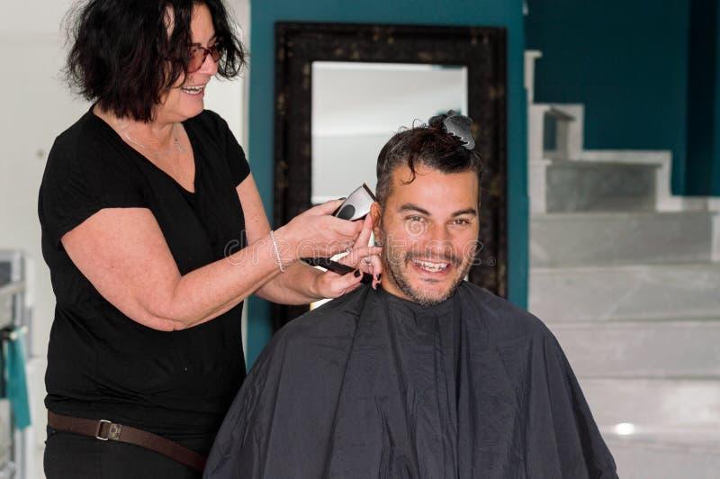 Weiblicher Friseur, der mit dem Haarscherer, jungen Männerkopf rasierend arbeitet lizenzfreie stockfotos