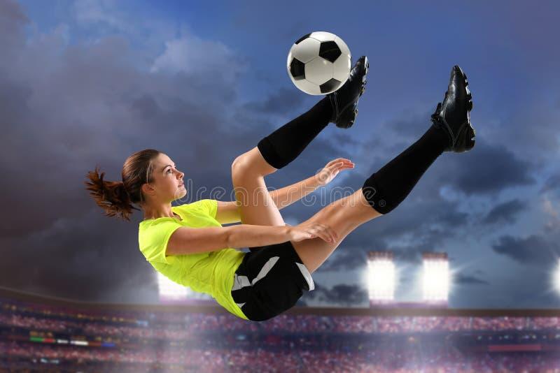 Weiblicher Fußball-Spieler, der Fahrrad-Tritt durchführt stockbild
