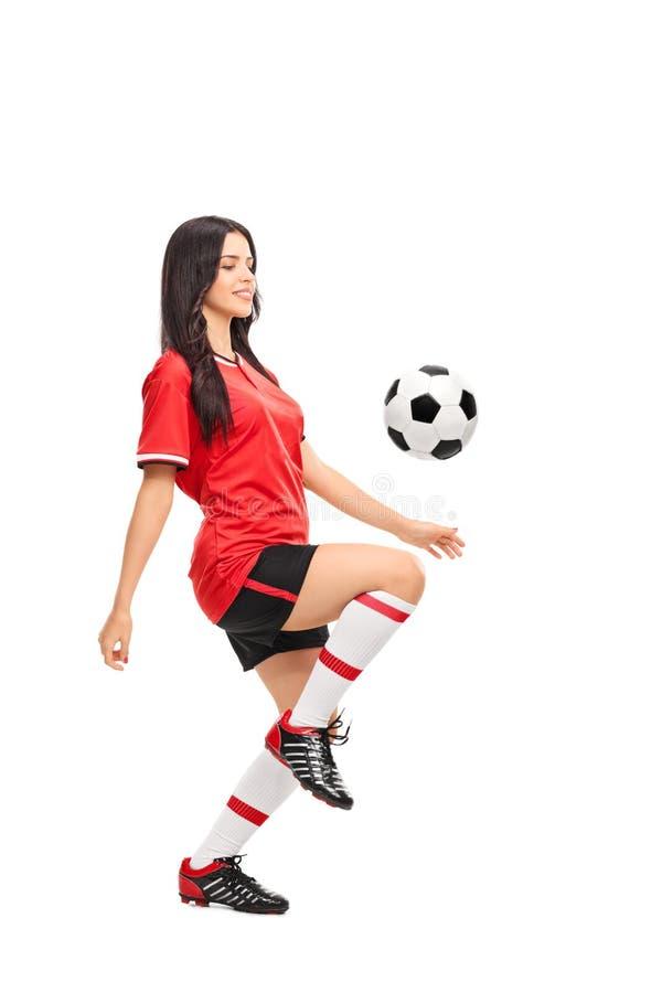 Weiblicher Fußballspieler, der einen Ball jongliert lizenzfreie stockfotografie