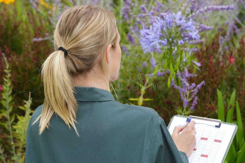 Weiblicher Gärtner, der Kenntnisse über Klemmbrett nimmt lizenzfreie stockbilder