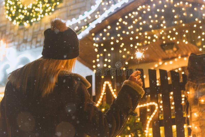 Weiblicher genießender Weihnachtsabend draußen mit Wunderkerzen stockfoto