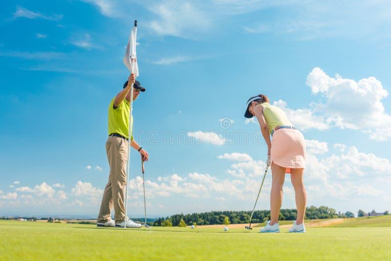 Weiblicher Golfspieler bereit, den Ball unter der Anweisung eines Golflehrers zu schlagen lizenzfreies stockfoto