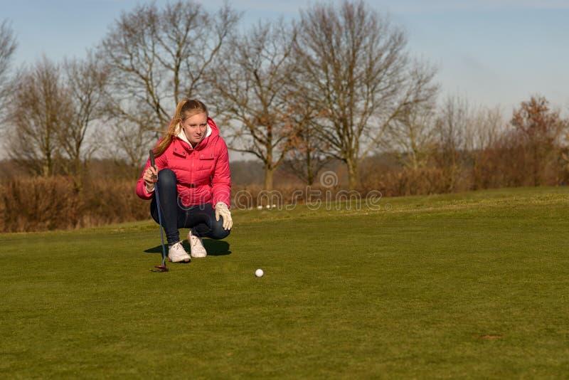 Weiblicher Golfspieler, der einen Schlag ausrichtet lizenzfreie stockfotos