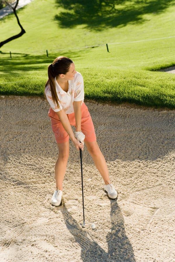 Weiblicher Golfspieler, der Kugel schlägt lizenzfreie stockbilder