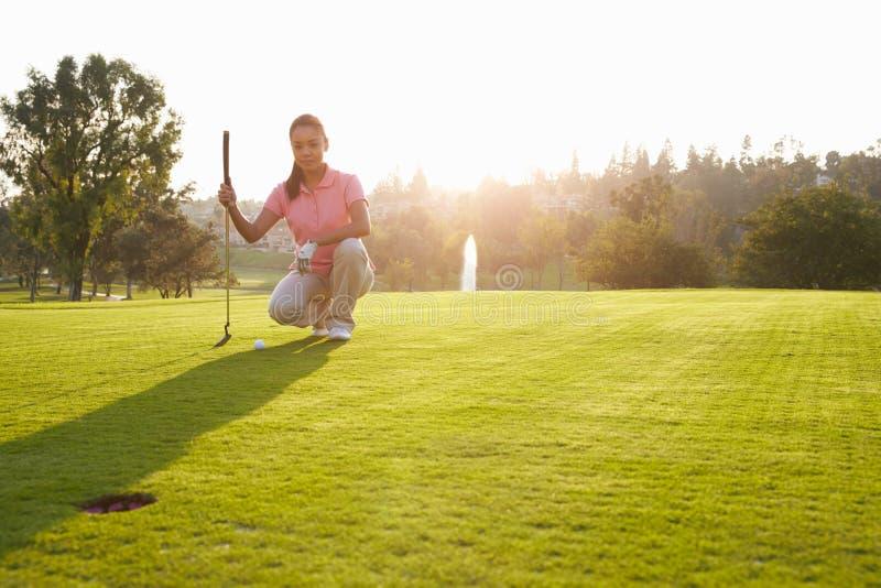 Weiblicher Golfspieler, der Schlag auf Grün ausrichtet stockbilder