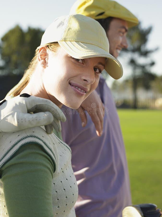 Weiblicher Golfspieler mit Freunden auf Golfplatz stockfoto