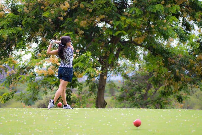 Weiblicher Golfspieler schlägt Golfball lizenzfreie stockbilder