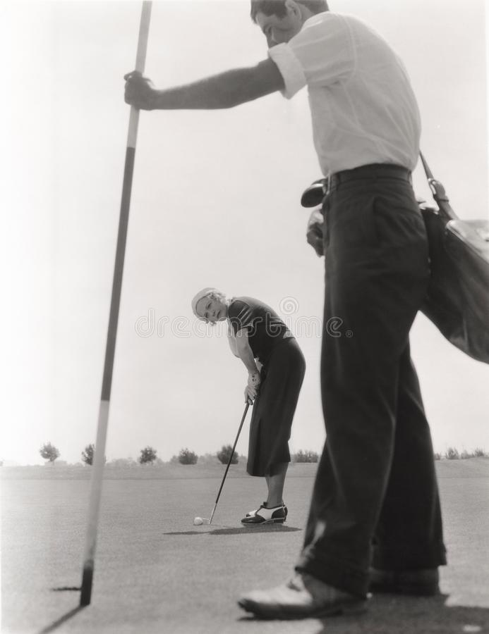Weiblicher Golfspieler und ihr Transportgestell stockbilder