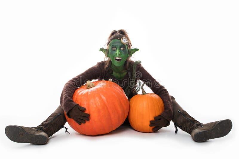 Weiblicher grüner Kobold mit Kürbisen, Halloween stockfotos