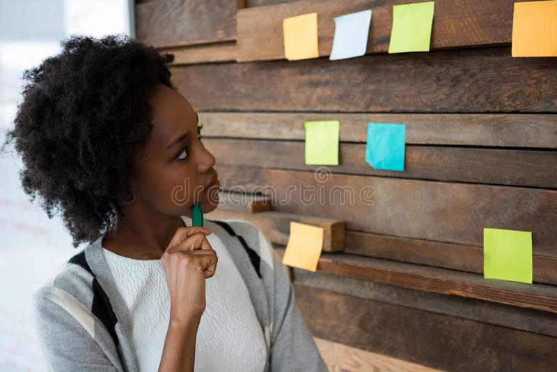 Weiblicher Grafikdesigner, der auf klebrige Anmerkungen zeigt stockbilder