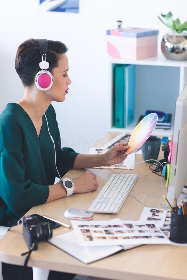 Weiblicher Grafikdesigner, der an Computer am Schreibtisch arbeitet lizenzfreies stockbild