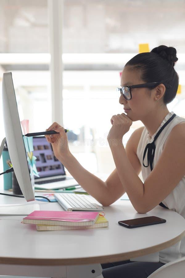 Weiblicher Grafikdesigner, der an Computer am Schreibtisch in einem modernen Büro arbeitet lizenzfreie stockfotografie