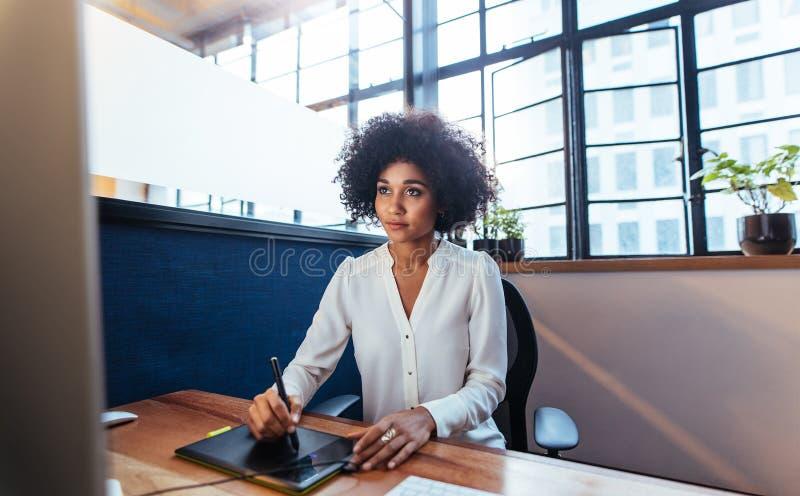 Weiblicher Grafikdesigner, der mit digitaler grafischer Tablette arbeitet stockfoto