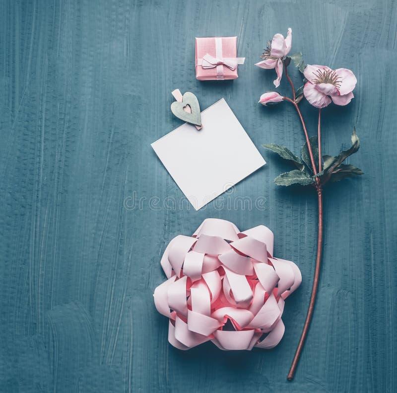 Weiblicher Grußhintergrund mit dekorativen Blumen, Bogen, rosa Geschenkbox und Kartenspott oben, Draufsicht stockbild
