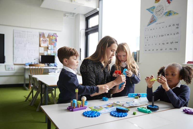 Weiblicher Grundschullehrer, der bei Tisch mit Kindern in einem Klassenzimmer, arbeitend zusammen mit Spielzeugbaublöcken sitzt stockbild
