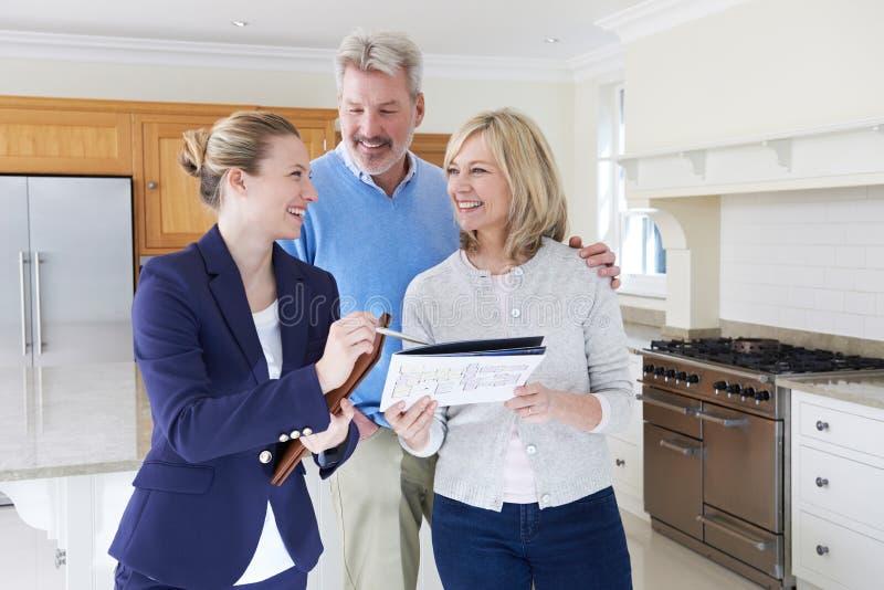 Weiblicher Grundstücksmakler, der reife Paare um Haus zu verkaufen zeigt stockbilder