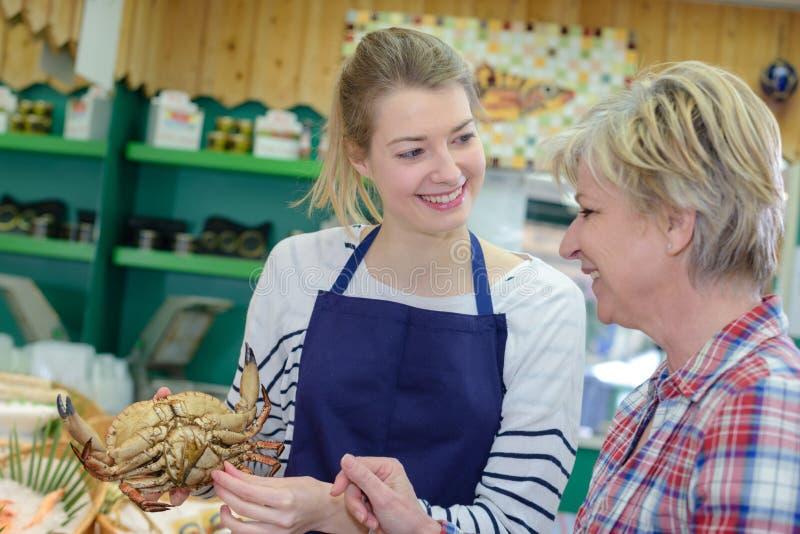Weiblicher Händler, der dem Kunden Krabbe zeigt lizenzfreie stockfotografie