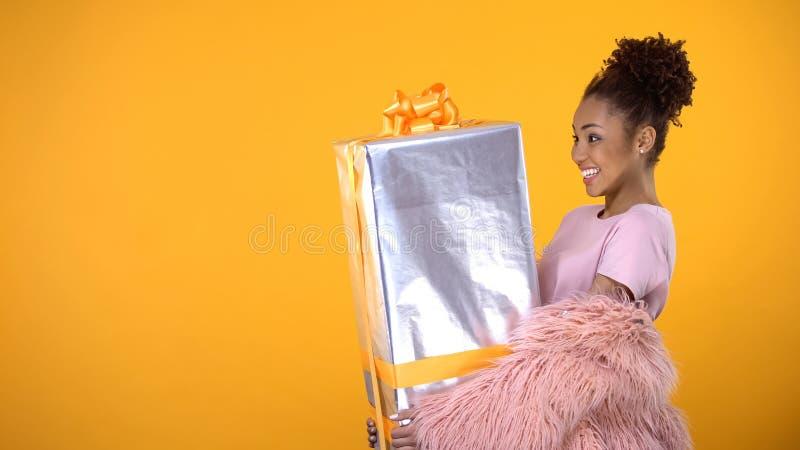 Weiblicher haltener heller Hintergrund des großen Präsentkartons des hübschen Afrikaners, Geschenkglück stockfotos