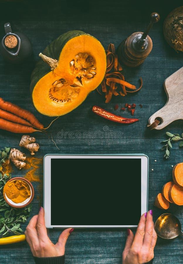 Weiblicher Handholding-Tabletten-PC mit leerem schwarzem Schirmspott oben auf Küchentischhintergrund mit Kürbis- und Gemüsebestan stockfoto