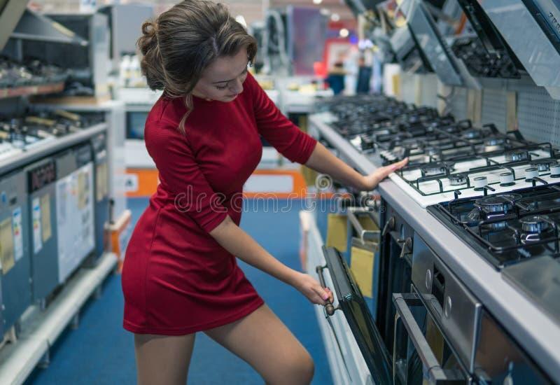 Weiblicher Hausfraukunde, der großen Gasherd wählt stockbild