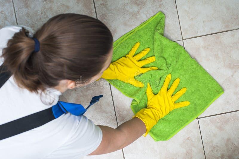 Weiblicher Hausmeister, der Keramikziegel wäscht stockfotografie