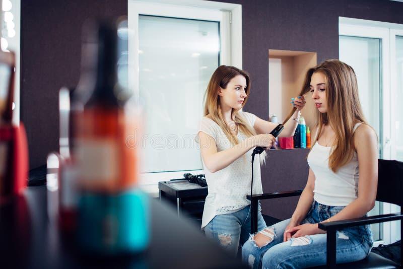 Weiblicher Herrenfriseur, der Haar des recht jungen blonden Kunden am Frisurnschönheitssalon geraderichtet stockfotos