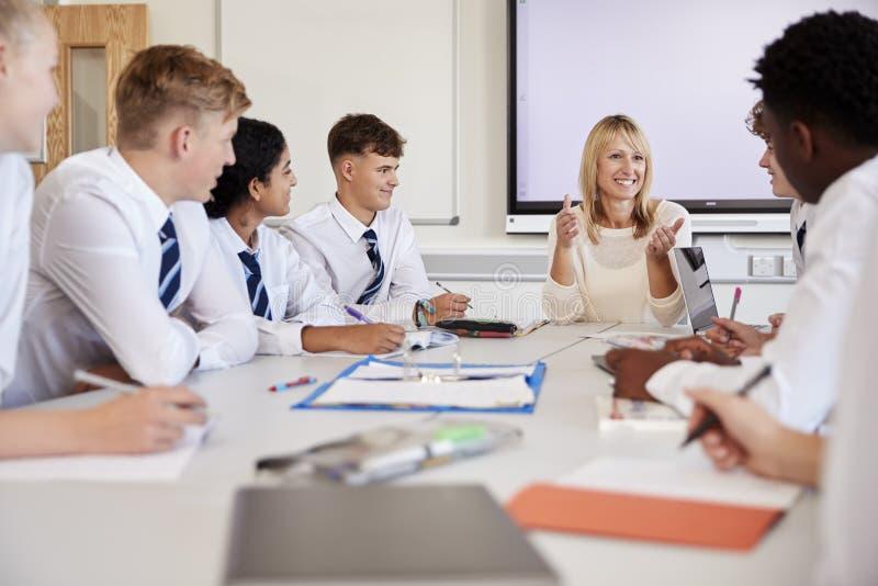 Weiblicher Highschoollehrer Sitting At Table mit den Jugendschülern, die einheitliche unterrichtende Lektion tragen stockfotografie