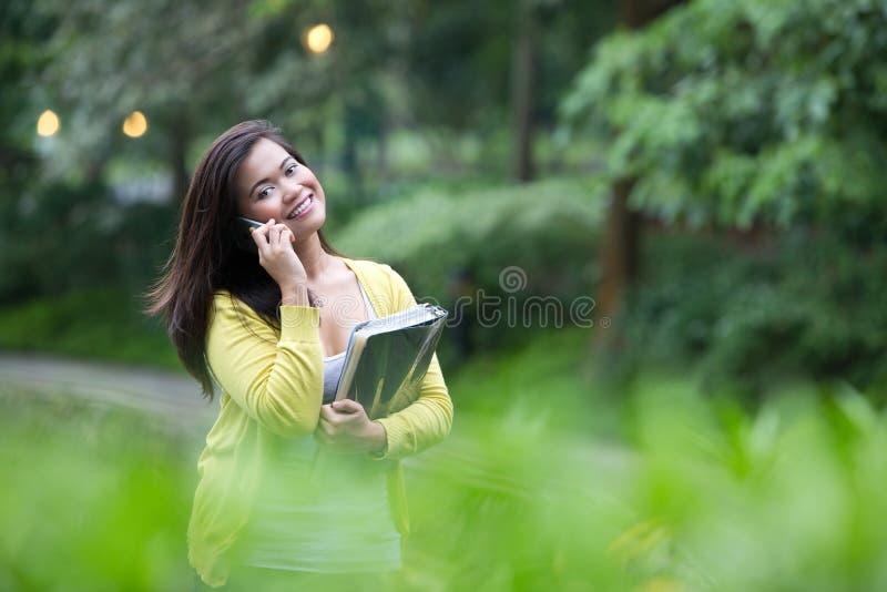 Weiblicher Hochschulstudent, der ihr Telefon, stehend in einem Park verwendet stockbilder