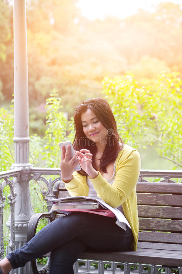 weiblicher Hochschulstudent mit Büchern und Dateien auf dem Schoss, drückend knöpft an ihrem Telefon stockbilder