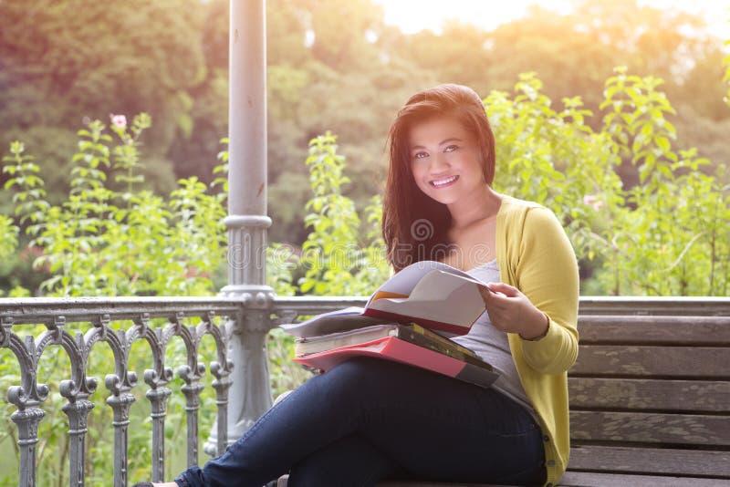 weiblicher Hochschulstudent mit Büchern und Dateien auf Schoss lizenzfreie stockbilder